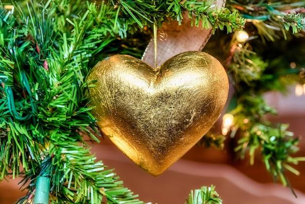 Mooie close-up van een gouden hartvormig ornament op een kerstboom met verlichting Gratis Foto