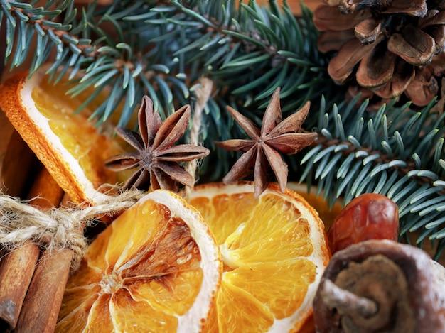 Mooie close-uptakken van sparren, droge sinaasappels, kaneelstokjes en steranijs, gedroogd fruit Premium Foto