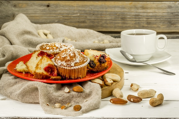Mooie cupcakes met bessen op houten achtergrond in rode plaat Gratis Foto