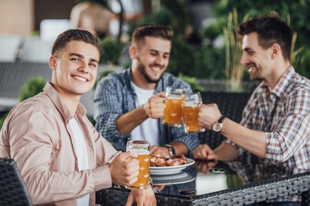 Mooie dag, drie zakenman zitten in zomerterras in café, en bier drinken. Premium Foto