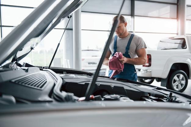 Mooie dag. man in blauw uniform werkt met kapotte auto. reparaties maken Gratis Foto