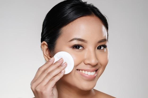 Mooie dame die haar gezicht met wattenschijfje schoonmaakt Gratis Foto