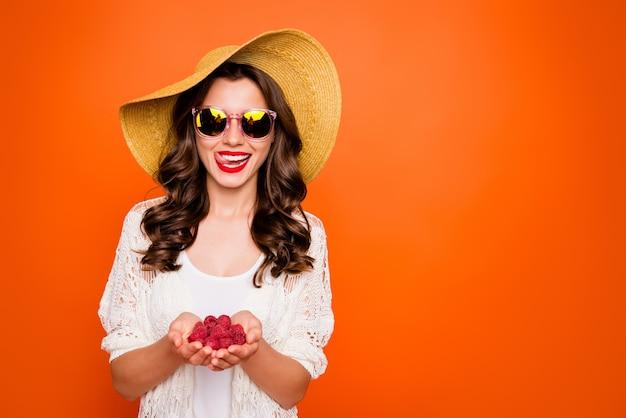 Mooie dame geniet van de zomervakantie met verse frambozen hongerige liklippen dragen pamela hoed Premium Foto