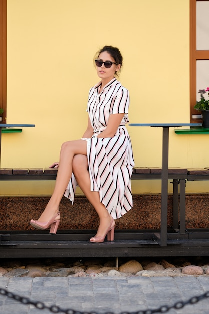 Mooie dame in gestreepte jurk zittend op een bankje Premium Foto