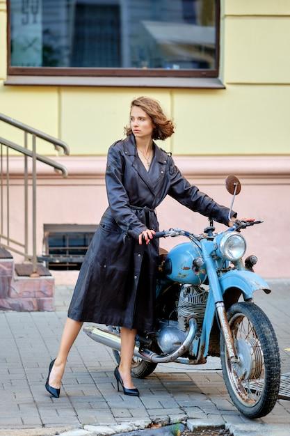 Mooie dame in lange leren jas met oude vintage motor Premium Foto