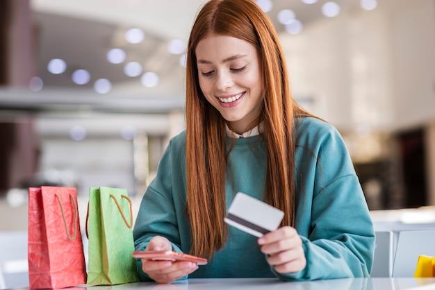 Mooie dame met telefoon en creditcard Gratis Foto