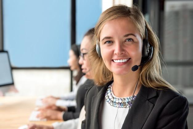 Mooie de dienstagent die van de vrouwenklant in call centre met haar team werkt Premium Foto