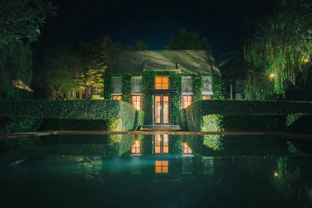 Mooie decoratie van engelse landelijke stijl gebouw bedekt met groene klimplant 's nachts Premium Foto