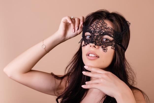 Mooie donkerbruine vrouw die elegant masker voor maskerade draagt dat over bruin wordt geïsoleerd Premium Foto