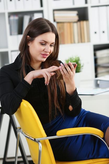 Mooie donkerbruine vrouw in de telefoon van de bureaugreep op het werk Premium Foto