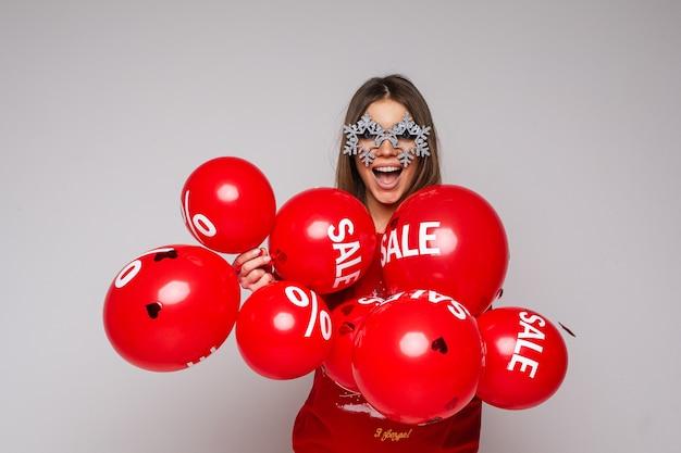 Mooie donkerbruine vrouw in mooie glazen met sneeuwvlokken die luchtballons houden Premium Foto