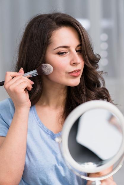 Mooie donkerbruine vrouw met borstel en spiegel die make-up doet Gratis Foto