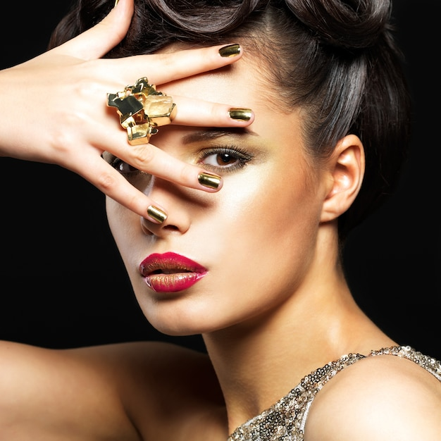 Mooie donkerbruine vrouw met gouden spijkers en stijlmake-up van ogen Gratis Foto