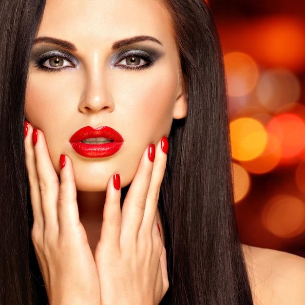 Mooie donkerbruine vrouw met rode lippen en spijkers. gezicht van een mooi meisje op de achtergrond van nachtverlichting Gratis Foto