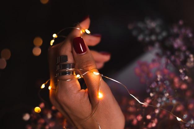 Mooie donkere foto van de handvingers van de vrouw met grote zilveren ring van bloemen en gloeiende lichten Gratis Foto