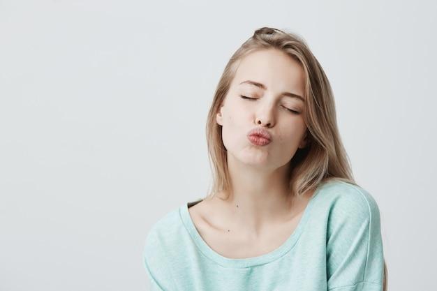 Mooie dromerige vrouw met blond haar sluit ogen, pruilt lippen, stuurt kusjes Gratis Foto
