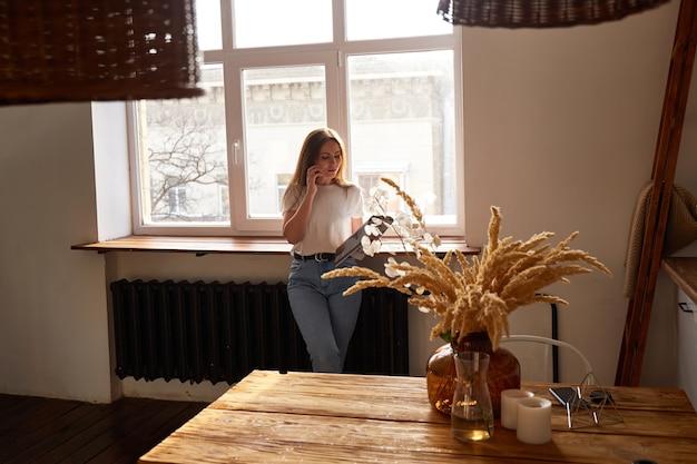 Mooie duizendjarige vrouw met behulp van mobiele telefoon en lachend terwijl je in de buurt van keukenraam. natuurlijk ochtendlicht. online chatten of winkelen Premium Foto