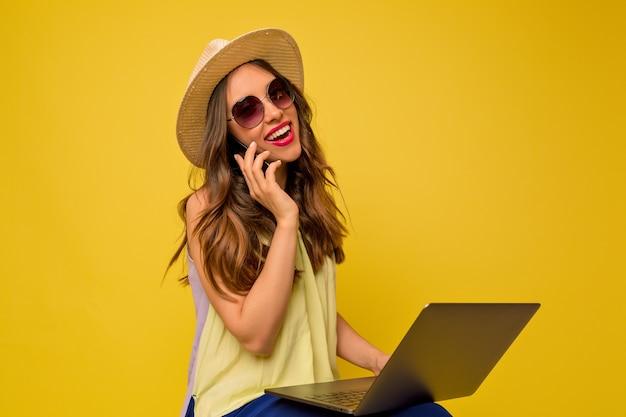 Mooie effectieve vrouw met hoed en zomerjurk lopen aan de telefoon en werken met laptop Gratis Foto