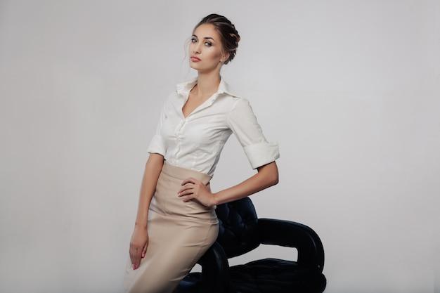 Mooie elegante jonge bussinesvrouw die zich op de studio met grijze achtergrond bevinden Premium Foto