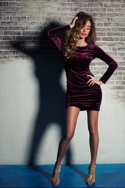 Mooie elegante jonge vrouw met lichtbruin haar poseren in bourgondische fluwelen jurk en gouden hakken Premium Foto