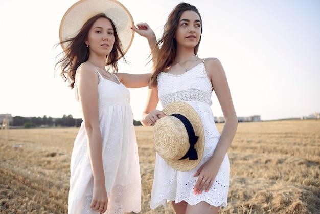 Mooie elegante meisjes op een gebied van de de herfsttarwe Gratis Foto
