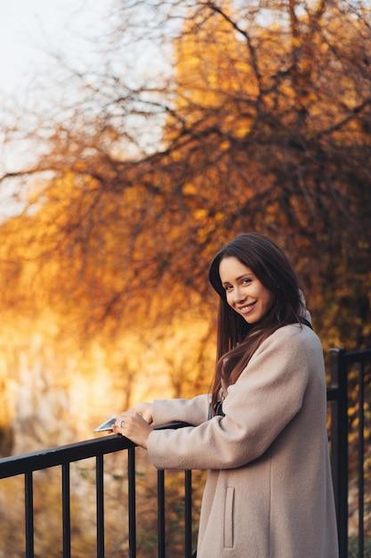 Mooie elegante vrouw die zich in een park in de herfst bevindt Gratis Foto