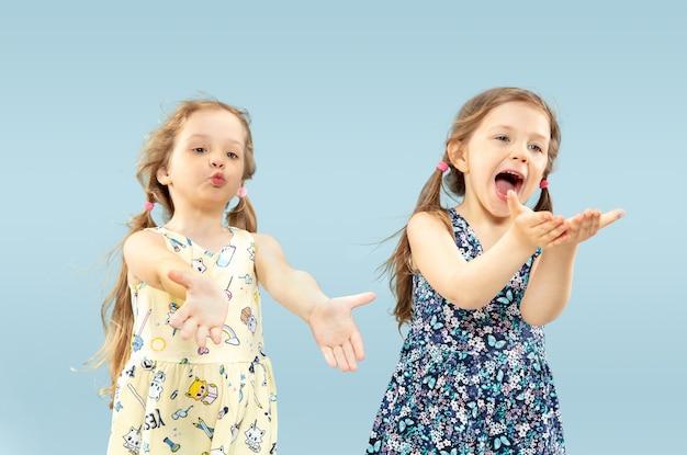 Mooie emotionele kleine meisjes geïsoleerd. portret van gelukkige zusters of vrienden die jurken dragen en spelen. concept van gezichtsuitdrukking, menselijke emoties, kindertijd. Gratis Foto