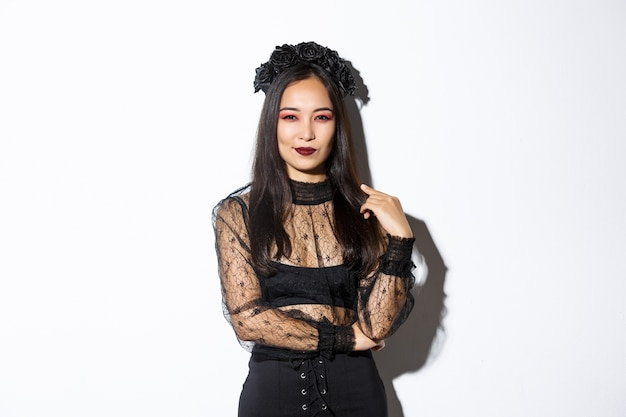 Mooie en brutale aziatische vrouw gekleed in zwarte kanten jurk en krans voor halloween-feest. vrouw met gotische make-up glimlachend tevreden, camera zelfverzekerd kijken. Gratis Foto