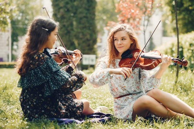 Mooie en romantische meisjes in een park met een viool Gratis Foto