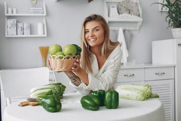 Mooie en sportieve vrouw in een keuken met groenten Gratis Foto