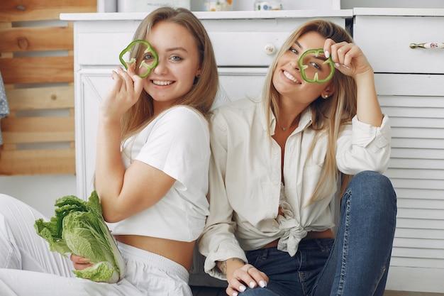 Mooie en sportieve vrouwen in een keuken met groenten Gratis Foto