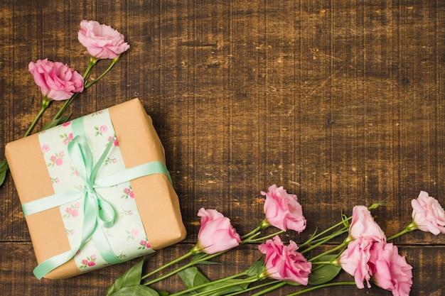 Mooie eustomabloem en decoratieve verpakte huidige doos over houten geweven Gratis Foto