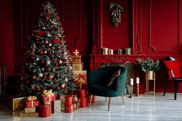 Mooie feestelijk versierde rode woonkamer met een kerstboom Premium Foto