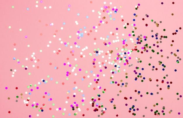 Mooie feestelijke pastelkleur roze achtergrond met rode metaalconfettien. Premium Foto