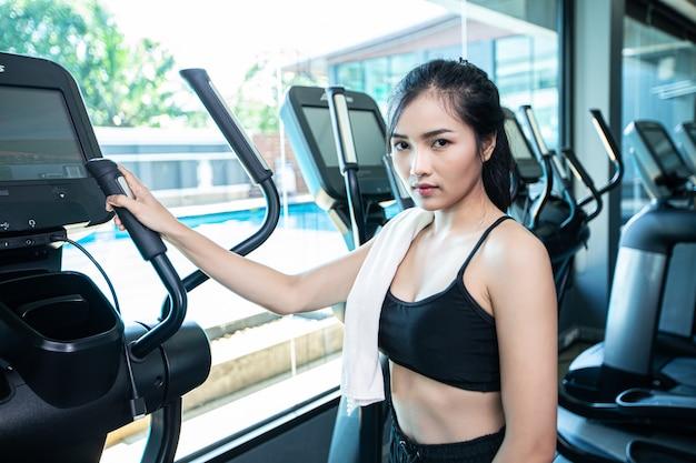 Mooie fitnessvrouwen bereiden zich voor op hardlopen op de loopband in de sportschool. Gratis Foto