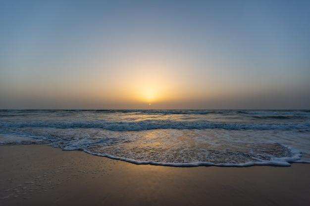 Mooie foto van een zonsondergang vanaf een strand onder een blauwe hemel in senegal Gratis Foto