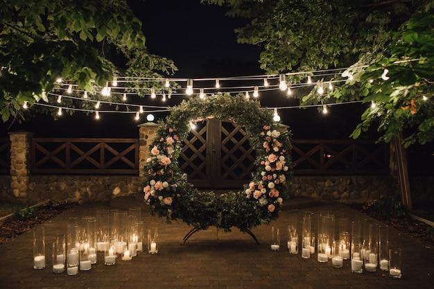 Mooie fotozone met grote krans versierd met groen en rozen in het middenstuk, kaarsen aan de zijkanten en slinger opgehangen tussen bomen Gratis Foto