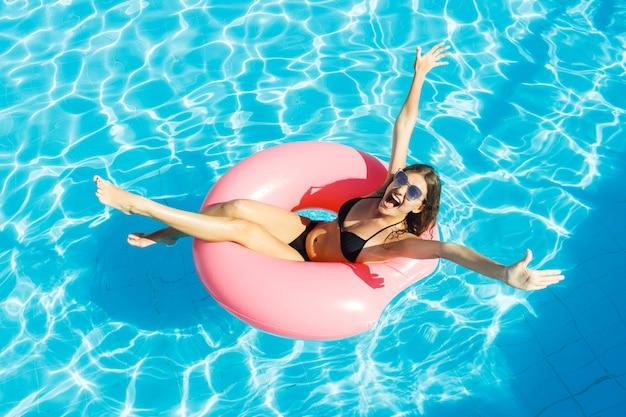 Mooie gekke vrouw ontspannen op opblaasbare ring in blauw zwembad Premium Foto