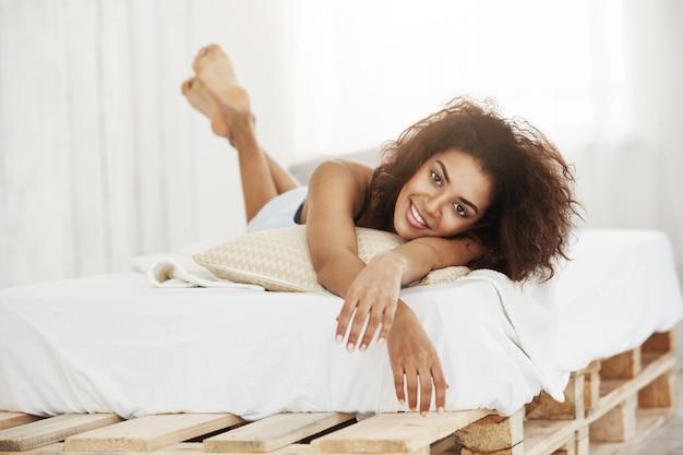 Mooie gelukkige afrikaanse vrouw die op bed ligt dat thuis glimlacht. Gratis Foto