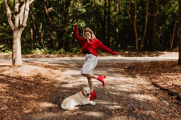 Mooie gelukkige blonde in rode trui genieten van geweldige tijd met haar labrador in het park. stijlvol meisje in warme kleren poseren onder gevallen gele bladeren. Gratis Foto