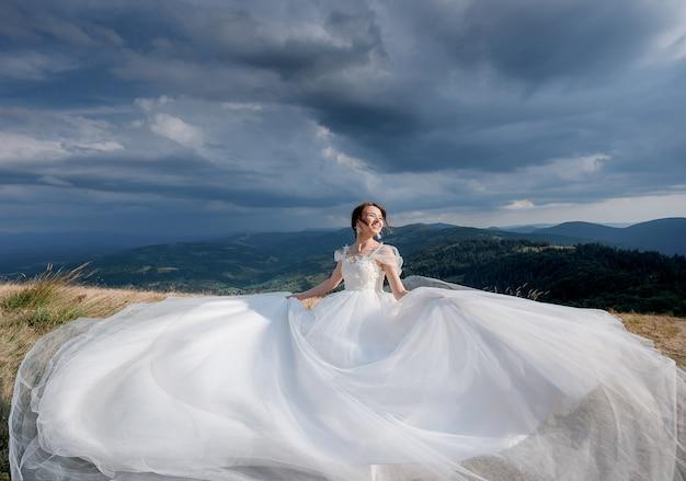 Mooie gelukkige bruid gekleed in luxe trouwjurk op de zonnige dag in de bergen met de bewolkte hemel Gratis Foto