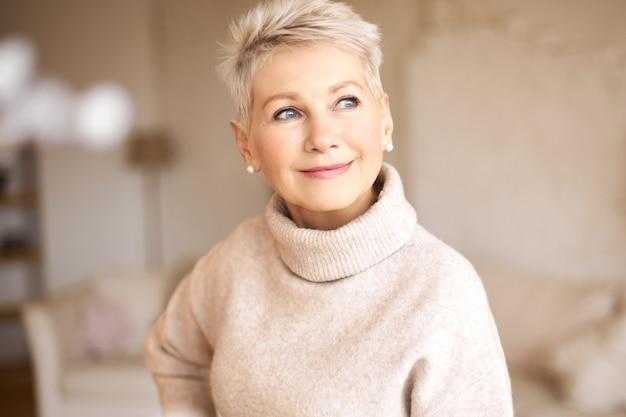 Mooie gelukkige gepensioneerde vrouw, gekleed in gezellige trui en kort kapsel Gratis Foto