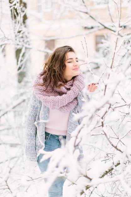 Mooie gelukkige jonge vrouw in een vintage mode blauwe trui en warme sjaal wandelen in de winter stad, staande in de buurt van de boom met sneeuw. wintervakantie en Premium Foto