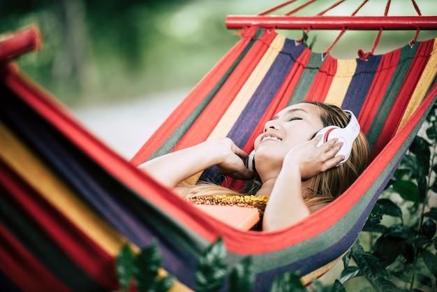 Mooie gelukkige jonge vrouw met een koptelefoon luisteren naar muziek Gratis Foto