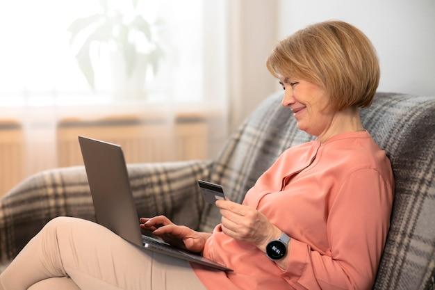 Mooie gelukkige oudere senior vrouw zittend op de bank thuis met laptop, online kopen met creditcard Premium Foto