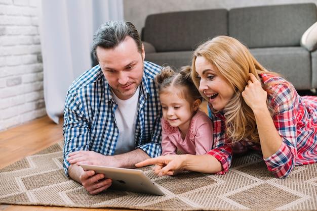 Mooie gelukkige ouders met hun kleine dochter die digitale tablet gebruiken Gratis Foto
