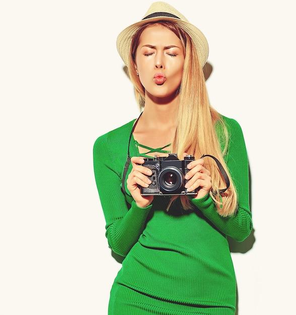 Mooie gelukkige schattige blonde vrouw meisje in casual zomer groene hipster kleding maakt foto's met retro fotografische camera, een kus geven Gratis Foto