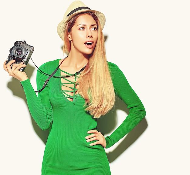 Mooie gelukkige schattige blonde vrouw meisje in casual zomer groene hipster kleding maakt foto's met retro fotografische camera Gratis Foto