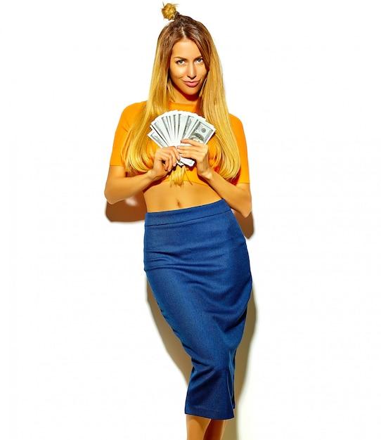Mooie gelukkige schattige lachende blonde vrouw meisje in casual kleurrijke hipster zomer kleding zonder make-up houden dollar bankbiljetten Gratis Foto