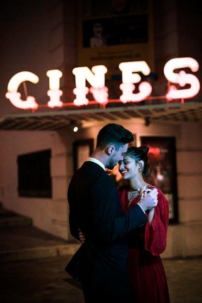 Mooie gelukkige vrouw hand in hand met jonge man op straat Gratis Foto